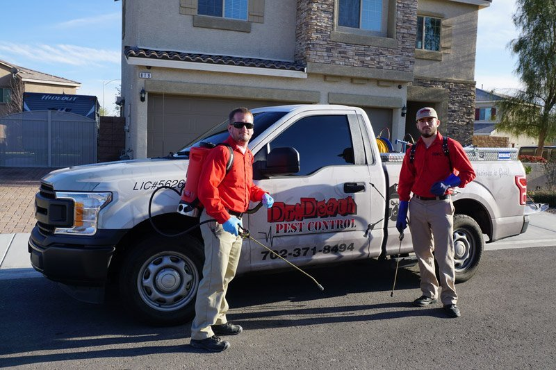 Two exterminators from Dr Death Pest Control standing near a truck